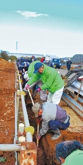 農業専用地区のU字溝の土をかき出す参加者