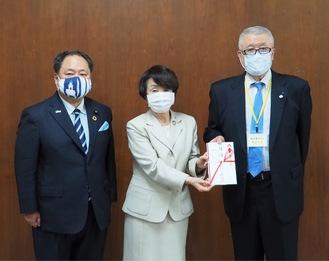 目録を手渡す轟ガバナー(右)。中央は林市長、隣は横山議長