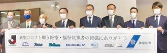感謝の横断幕をアピールする村井チェアマン(右から4人目)と黒岩知事(右から5人目)、クラブ幹部ら