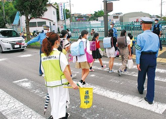 通学児童を見守る警察官ら