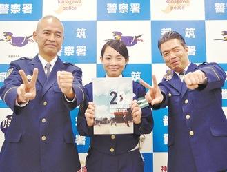 冊子を手にする太田巡査(中央)と押部署長(左)、大和調査官