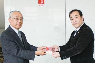 三科会長(左)からステッカーを受け取る吉田館長