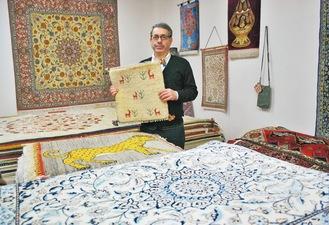 絨毯がずらりと並ぶ店内でサベリさん