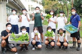 収穫した野菜を手に笑顔を見せるメンバー