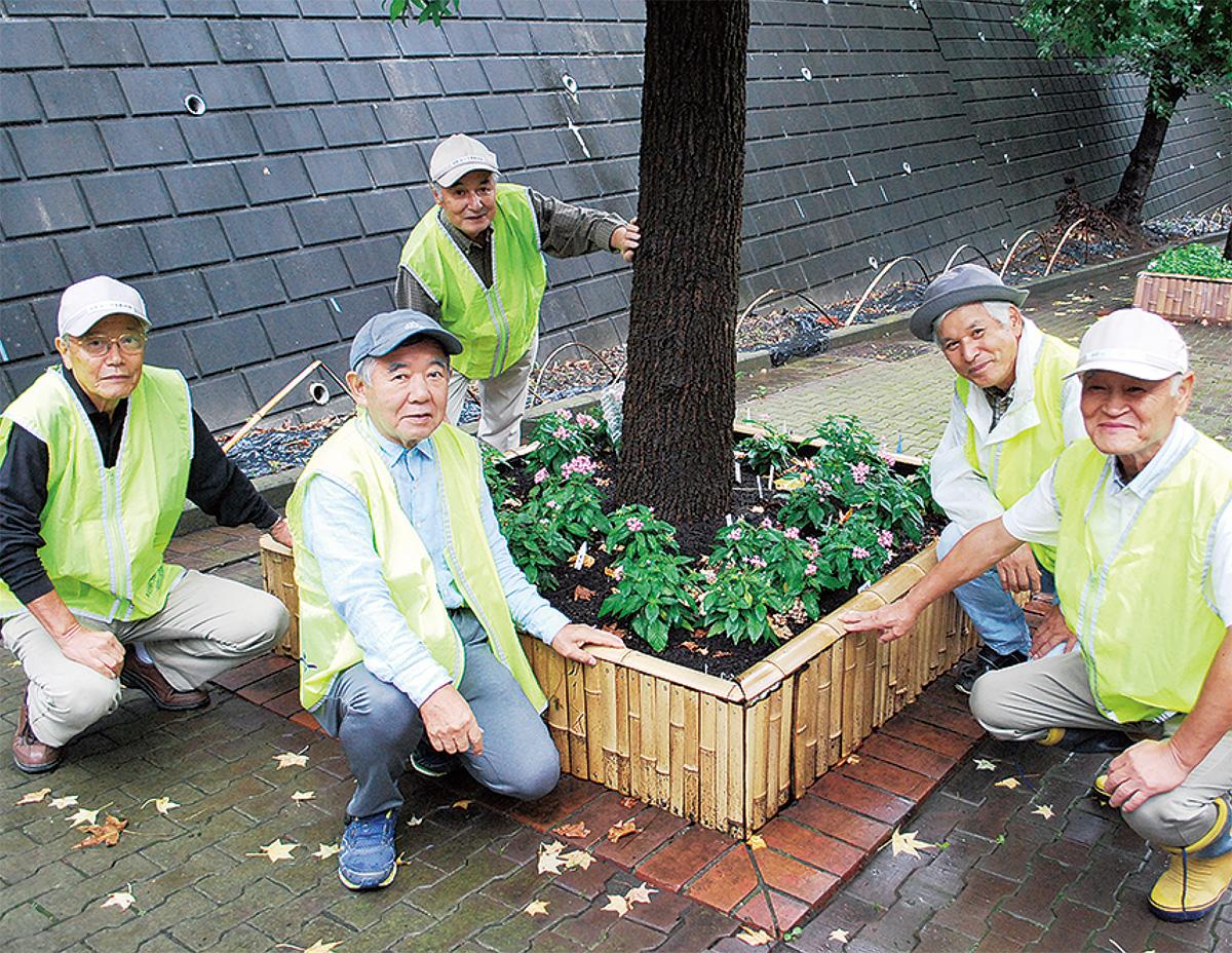 竹で囲んだ花壇と米山代表(右から二人目)、制作メンバー