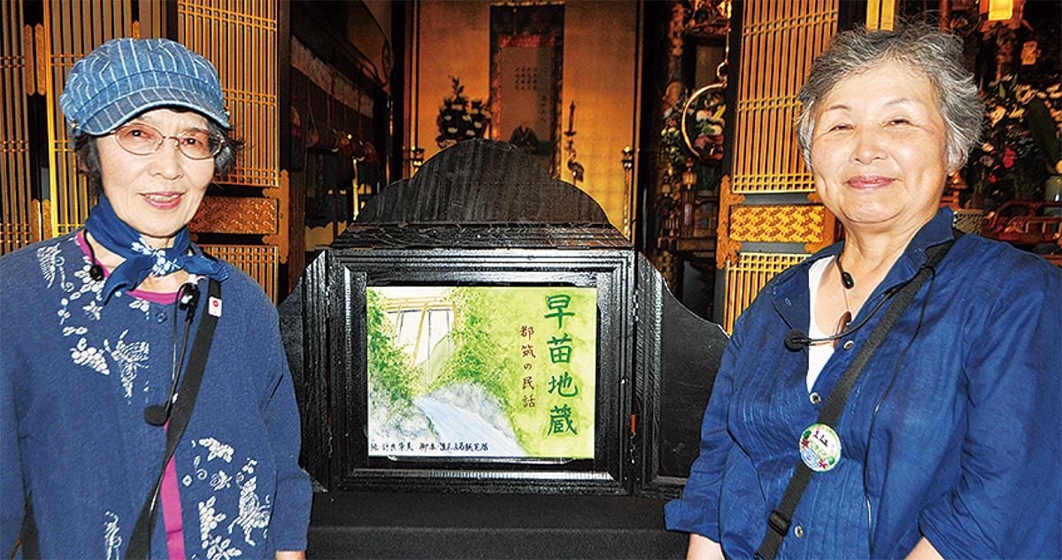 紙芝居の前に立つ三宅さん(左)と大橋さん
