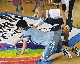 ボランティアと一緒に色を塗る参加児童