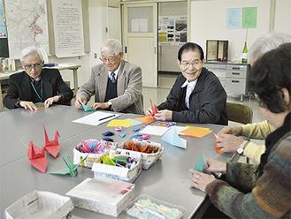 折り鶴コーナーで鶴を折る若葉の会のメンバー