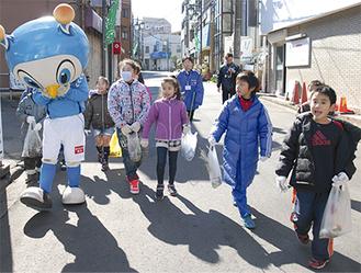 フリ丸(左)と、ごみを拾い歩く児童たち