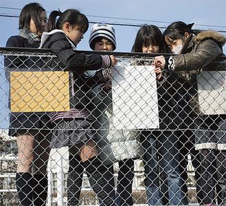 フェンスにポスターを掲示する児童たち