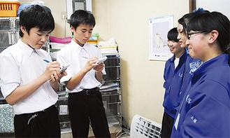 職場体験中の同級生を取材する、碓水君(右)と松村君