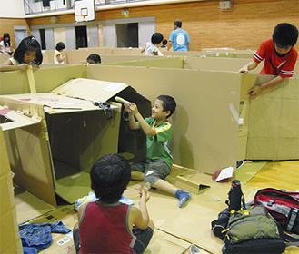 体育館を避難所に見立て、ダンボールで間仕切りなどを作る児童たち=18日