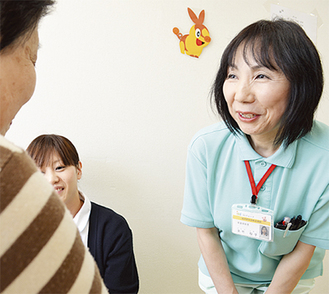 看護師と共に患者と談笑する矢竹さん(右)