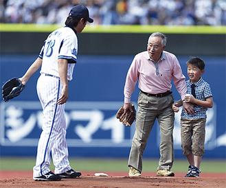 始球式で三浦投手(左)のもとへ向かう田中さん(中央)と孫・義樹君=球団提供
