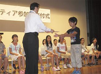 区長から参加証を受け取る地区代表の児童=旭区提供