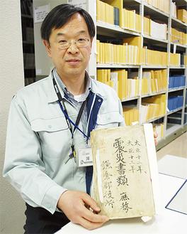 「関東大震災」の公文書を手に話す薄井さん