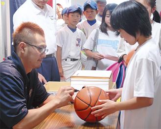ボールにサインする山田選手