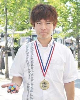 メダルをかけ、競技用のバッグを持つ石田さん