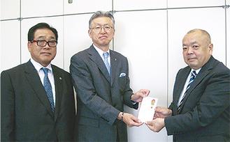支援金を手渡す山本会長(中)と柳室幹事(左)