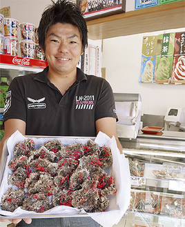 もずく天ぷらを手にする榎本さん