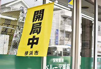 「開局中」の黄色い旗を掲出する薬局