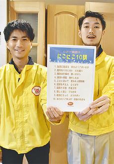 にこにこ10訓の表を見せる高木さん(左)と山崎さん
