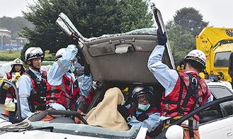 車体の一部を切断し、救助を行う消防隊員ら