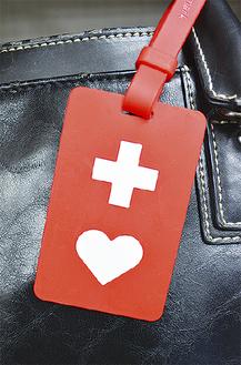 赤い樹脂製の素材に白い十字とハートが描かれたヘルプマーク
