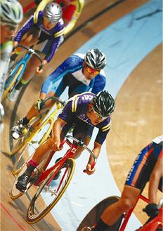 自転車で走る塩島君(写真右、本人提供)