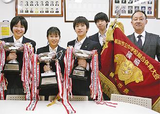 カップや優勝旗を手にする生徒たちと中村校長(右)