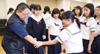 手をつかまれたときの護身術を署員から学ぶ生徒たち