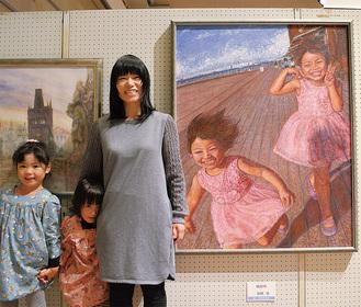 作品と並ぶ船橋さんとモデルとなった2人の娘たち