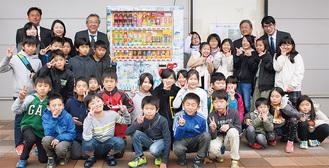 絵地図がラッピングされた自動販売機を囲む児童たちと関係者