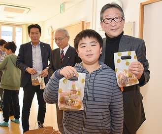 田中会長(右)ら会員から子どもへ直接手渡し