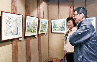 来場者に作品の解説をする木村さん(写真右)