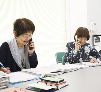 電話で話す酒井さん(左)と岩田さん