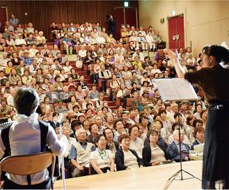 指揮と演奏に合わせて歌う参加者たち