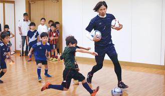 素早いボールさばきで子どもたちとゲームを行う鈴木さん