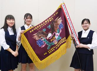 優勝旗を手にする奈良さん、野口さん、山内さん(右から)