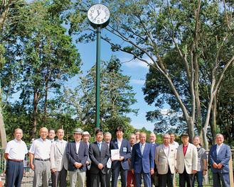 時計台を背景に記念撮影する同団体と区の関係者