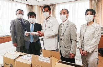 フェイスシールドを手渡す佐藤さん(左から2人目)ら旭RCの会員ら