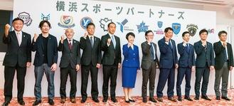 発足式に参加しガッツポーズを決めるチーム代表者(中央は林市長)