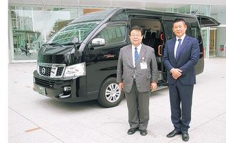 貸与する車両の前に立つ桑原社長(右)と田中局長