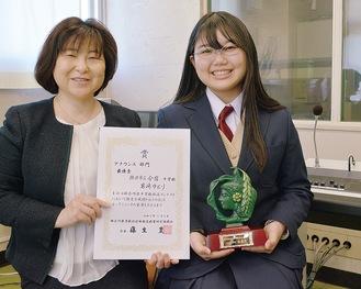 盾を手に笑顔を見せる岩崎さん(右)と熊野副校長