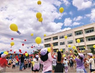 歓声を上げながら、風船を空に飛ばす児童たち