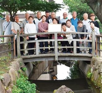 表彰状を手に活動場所の中堀川で笑顔をみせるメンバー