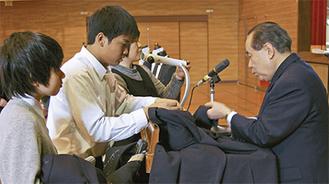 生徒の制服のボタンを付ける阿部さん(右)