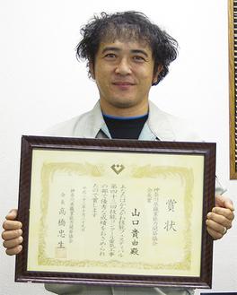 職能協会長賞を受賞し、笑顔の山口さん