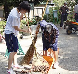 公園清掃を手伝う中学生