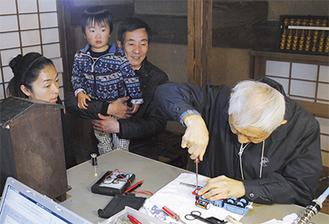 長屋門公園で修理を見守る子どもと家族